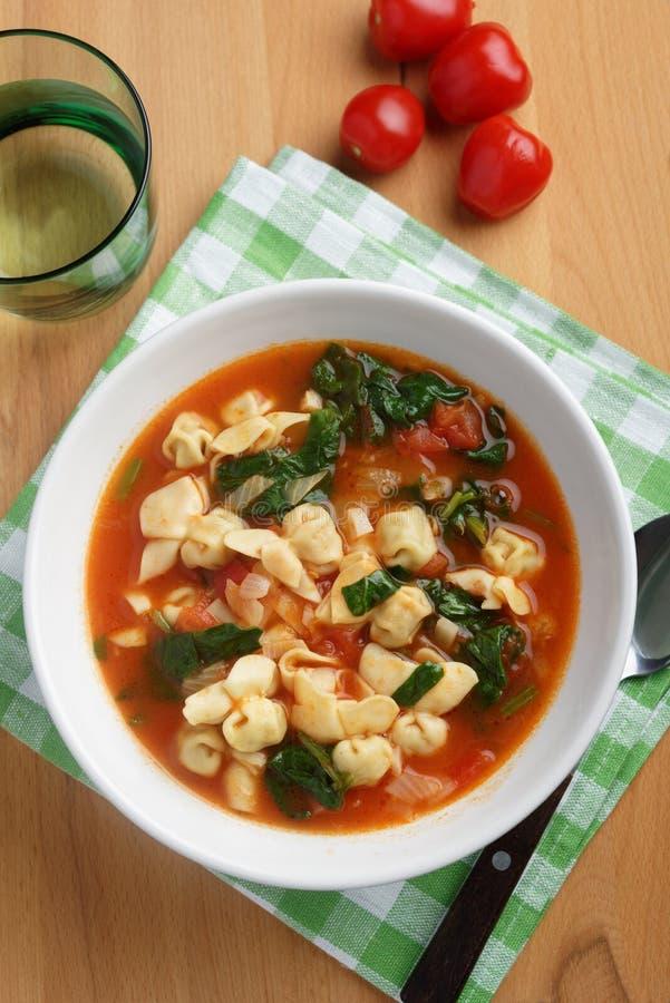 Sopa de la espinaca del tortellini del tomate imagen de archivo