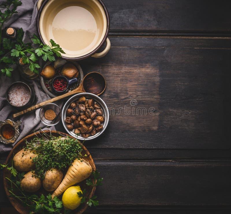 Sopa de las castañas que cocina los ingredientes con el pote y la cuchara en el fondo rústico oscuro, visión superior, lugar para imagenes de archivo