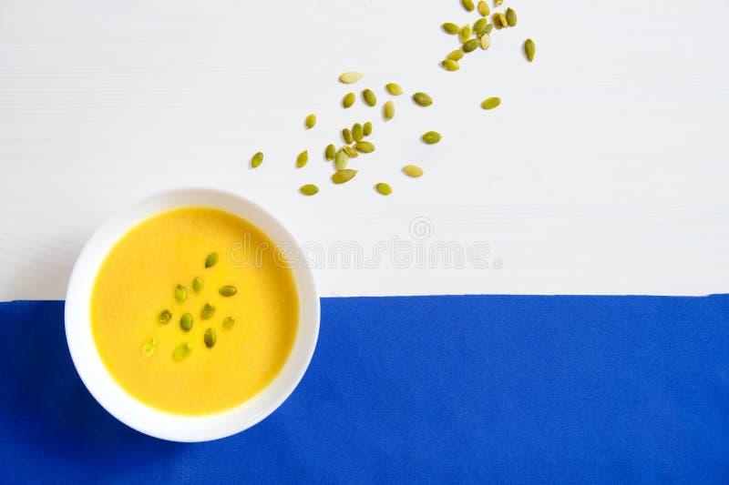 Sopa de las semillas de la calabaza y de girasol en una placa blanca en un fondo brillante El concepto de consumición sana, pérdi fotografía de archivo