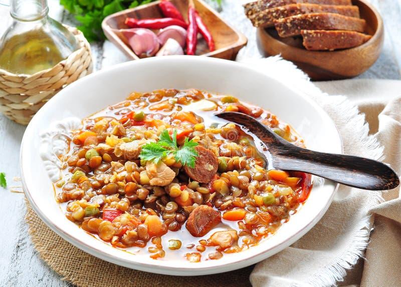Sopa de lenteja con el pollo y los salchichones salchicha, cebolla, zanahoria, pimienta dulce, ajo y perejil fotografía de archivo libre de regalías