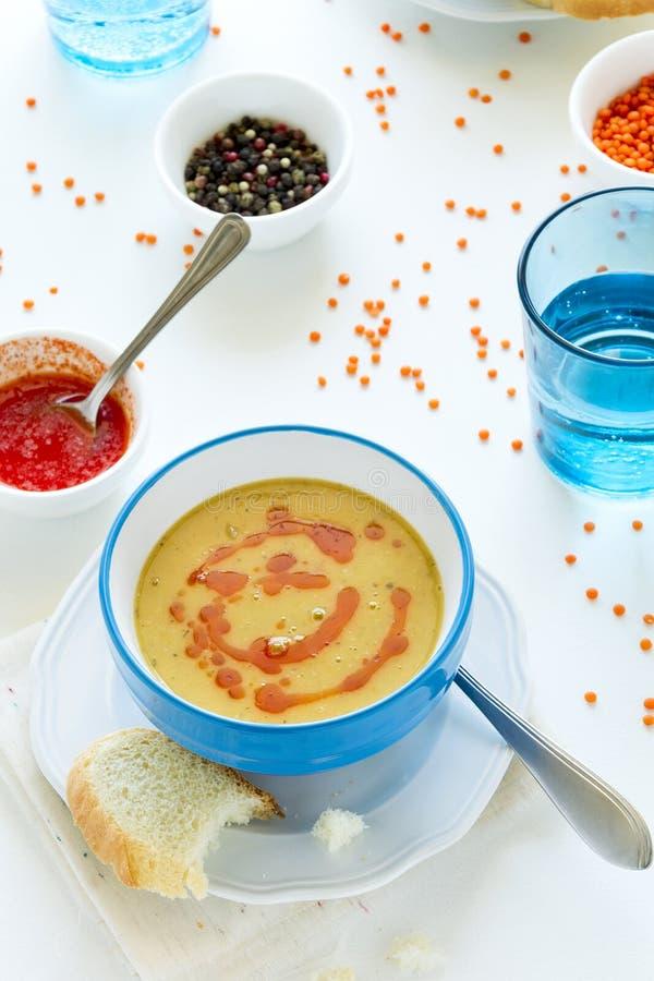 Sopa de lenteja roja con la salsa y el pan de pimienta de chile en la tabla de madera blanca imagen de archivo