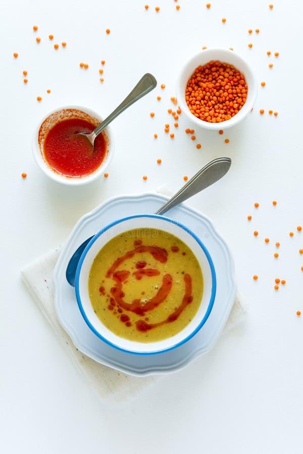 Sopa de lenteja roja con la salsa y el pan de pimienta de chiles en la tabla de madera blanca fotos de archivo