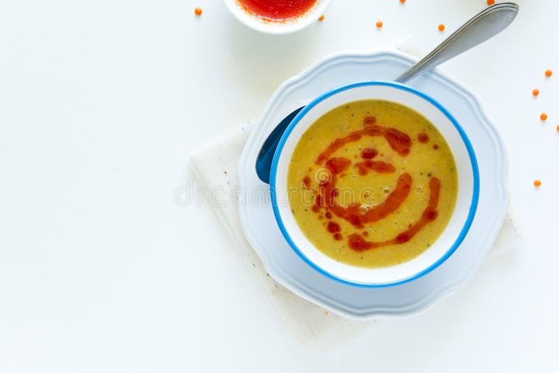 Sopa de lenteja roja con la salsa y el pan de pimienta de chiles en la tabla de madera blanca imagen de archivo