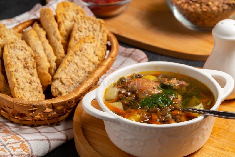 Sopa de lentilha com galinha em uma bacia branca em uma placa de madeira em uma tabela preta e em ingredientes fotografia de stock royalty free