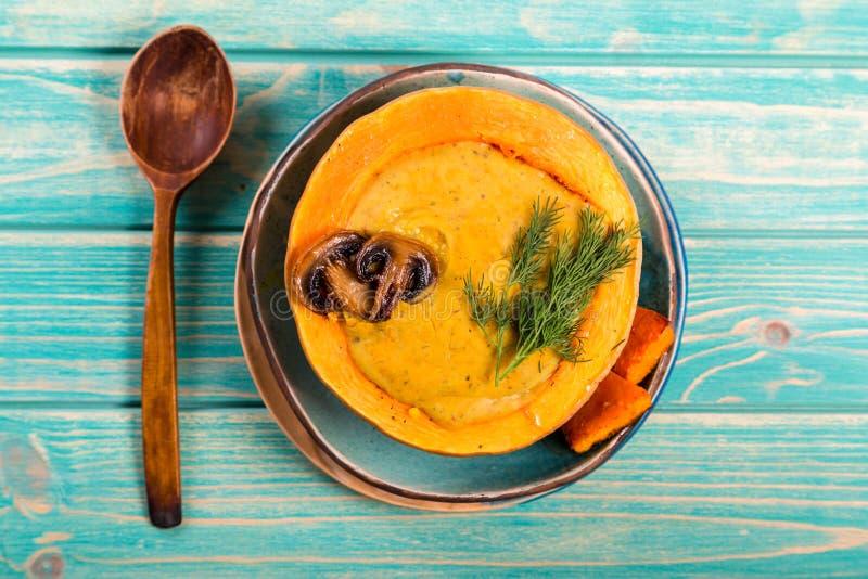 Sopa de lentilhas no prato da abóbora no fundo azul fotografia de stock royalty free