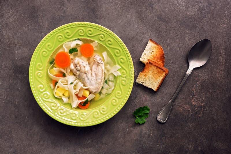 Sopa de macarronete da galinha, batatas, cenouras em uma placa verde servida com brindes fritados em um fundo rústico escuro Vist imagem de stock royalty free
