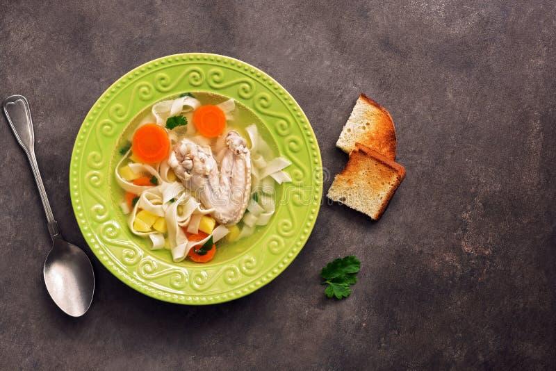 Sopa de macarronete da galinha, batatas, cenouras em uma placa verde servida com brindes fritados em um fundo rústico escuro Vist foto de stock royalty free