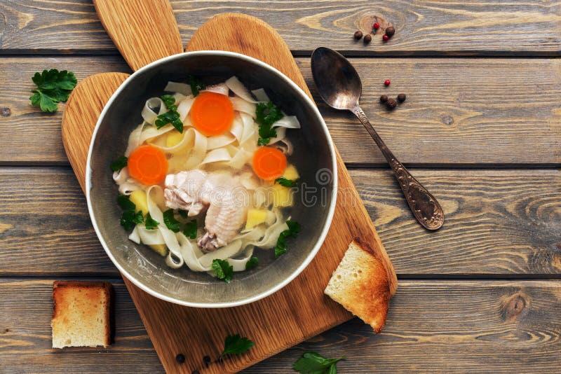 Sopa de macarronete da galinha em uma placa de corte com brinde, tabela de madeira da prancha Vista superior, configuração lisa imagens de stock royalty free