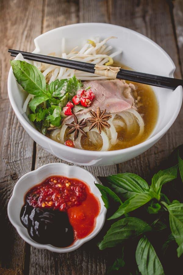 Sopa de macarronete de Pho Vietnamse na madeira velha A imagem para o alimento anuncia fotos de stock