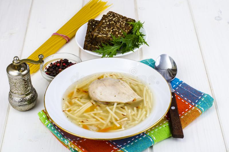 Sopa de macarronete do caldo de galinha no fundo de madeira branco imagens de stock
