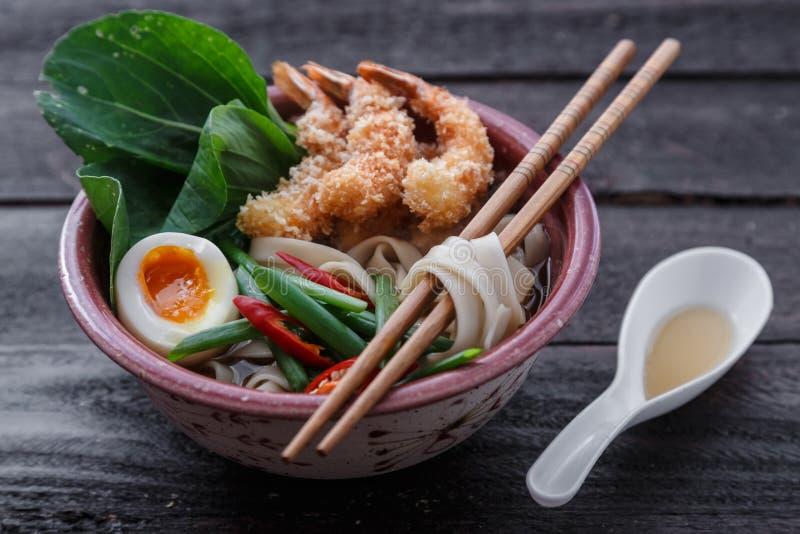 Sopa de macarronete japonesa coberta com camarões do tempura, ovo e verdes, vista próxima fotos de stock royalty free