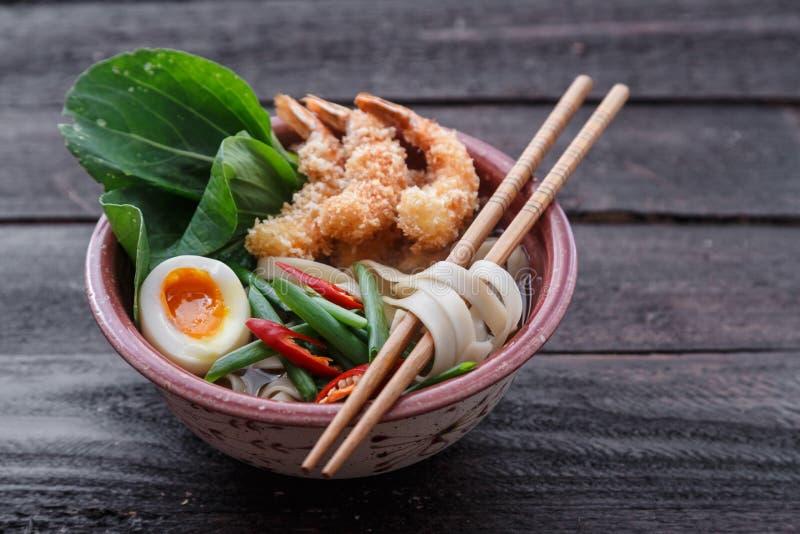 Sopa de macarronete japonesa coberta com camarões do tempura, ovo e verdes, vista próxima imagem de stock