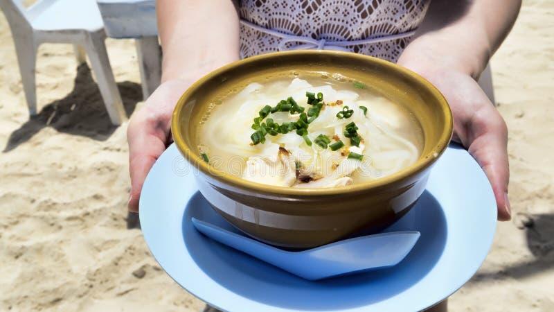 A sopa de macarronete tailandesa da galinha serviu na praia imagem de stock royalty free