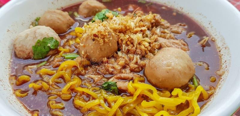 A sopa de macarronete tailandesa do ovo com a almôndega e a carne cortadas serviu em uma bacia imagens de stock