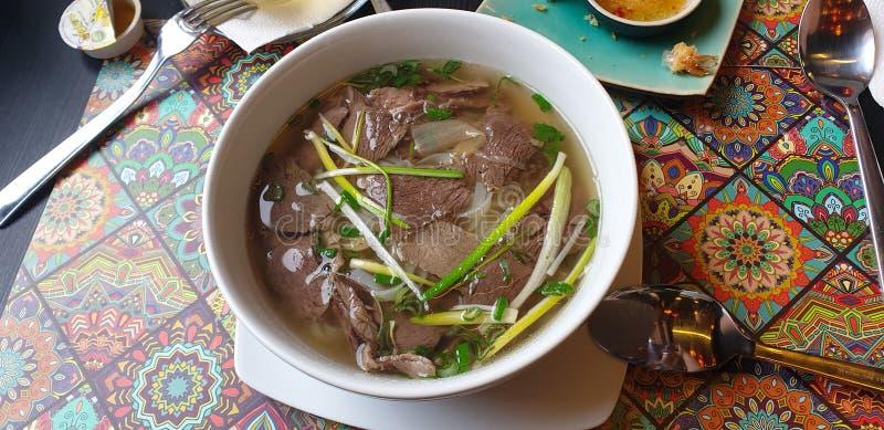 Sopa de Pho con carne de vaca y los tallarines en el restaurante tailandés en el timisoara Rumania fotos de archivo