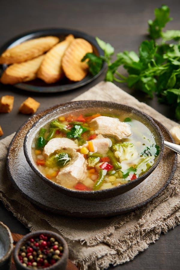 Sopa de pollo hecha en casa con las verduras, bróculi en el fondo marrón oscuro, vista vertical, lateral fotografía de archivo libre de regalías