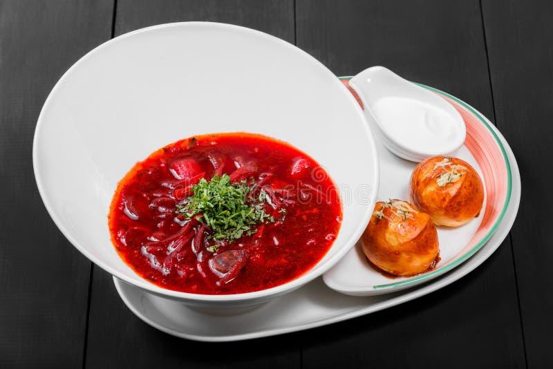 Sopa de remolachas tradicional ucraniana y rusa - borscht en placa, crema agria y bollos con ajo e hierbas en fondo oscuro foto de archivo