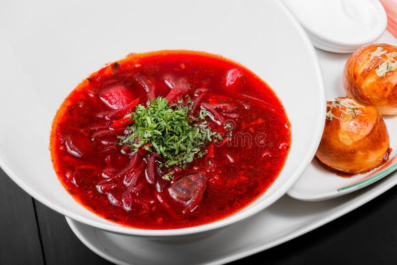 Sopa de remolachas tradicional ucraniana y rusa - borscht en placa, crema agria y bollos con ajo e hierbas en fondo oscuro fotos de archivo