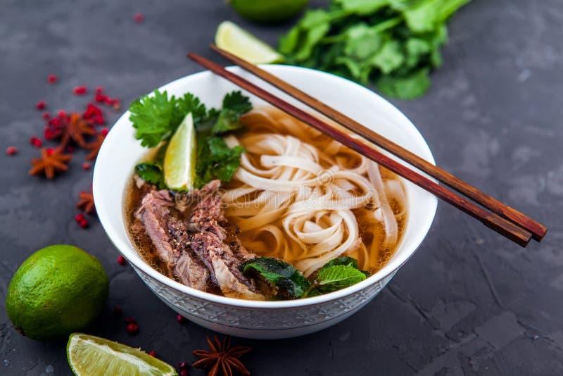 Sopa de tallarines vietnamita de Pho Carne de vaca con los chiles, albahaca, tallarines de arroz fotografía de archivo