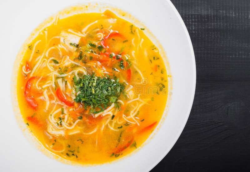 Sopa de verduras, caldo con los tallarines, hierbas, perejil y verduras en cuenco en el fondo negro de madera, comida sana fotografía de archivo libre de regalías