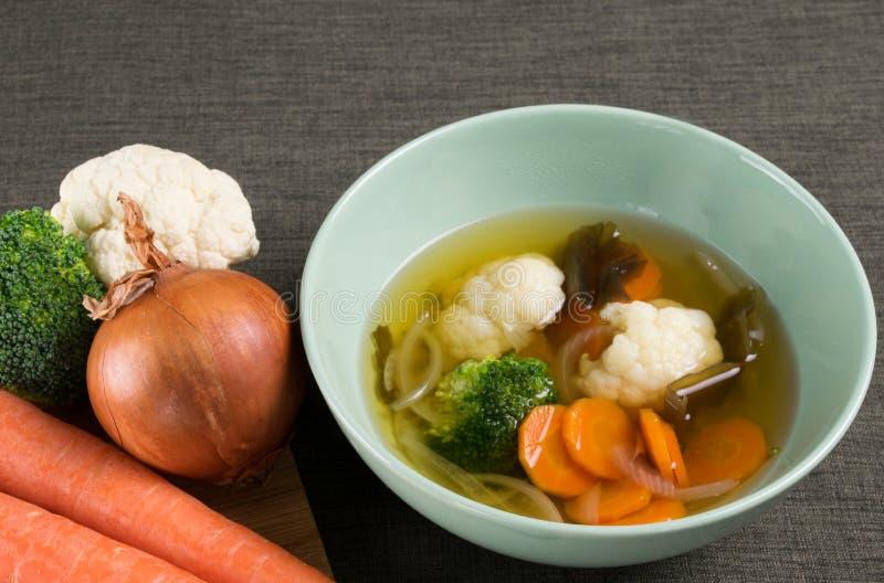 Sopa de verduras con la cebolla, zanahoria, coliflor, bróculi y alga marina en plato verde en mantel marrón, y verduras frescas t imagenes de archivo