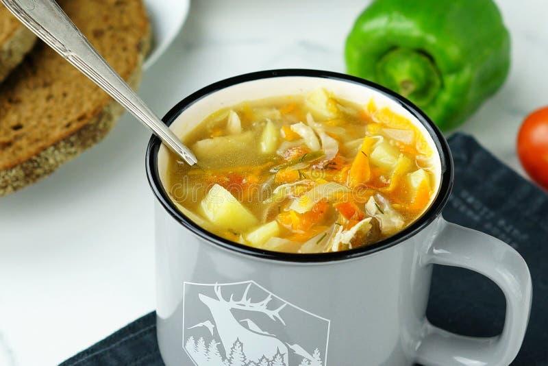 Sopa de verduras hecha en casa en taza del esmalte imagenes de archivo