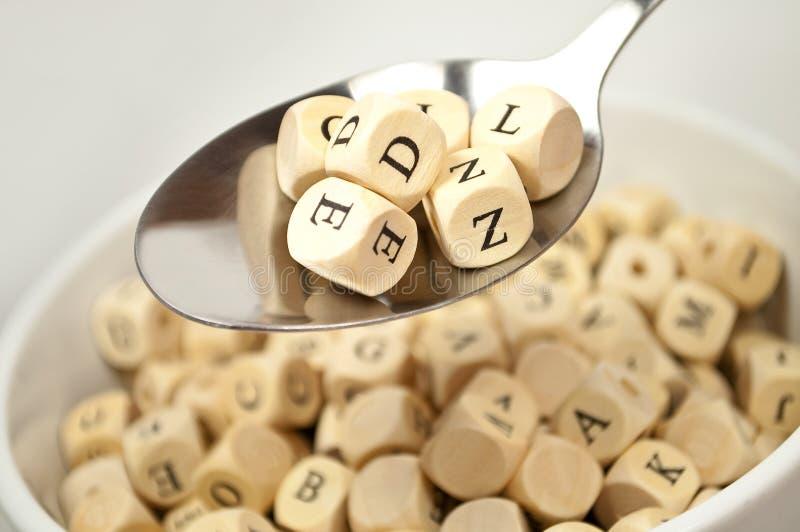 Sopa del alfabeto con los dados y la cuchara de los cubos fotografía de archivo