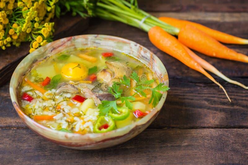 Sopa del arroz con los ombligos del pollo y la yema de huevo Fondo rústico de madera Visión superior Primer foto de archivo libre de regalías