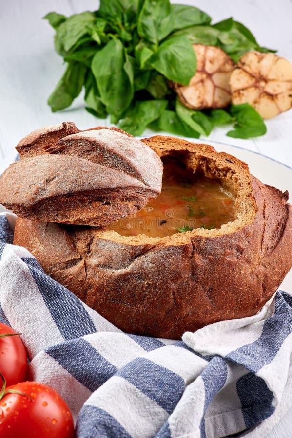 Sopa del cuenco del pan en la sobremesa de madera blanca La sopa del pan es plato checo tradicional de la cocina fotografía de archivo libre de regalías