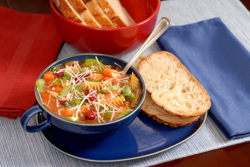 Sopa del Minestrone en tazón de fuente azul con pan italiano imagen de archivo