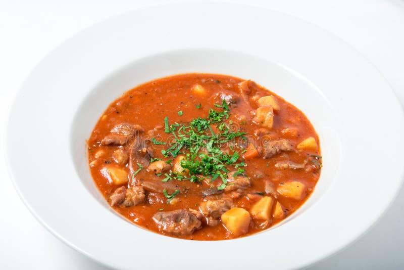 Sopa del tomate con la carne, patatas, zanahorias, parsternak en la placa blanca imagen de archivo