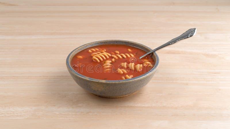 Sopa del tomate de Rotini en cuenco con la cuchara en la tabla imagen de archivo