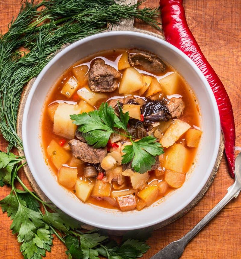 Sopa deliciosa con el cordero y las patatas con las hierbas en la placa blanca en un cierre de madera del fondo de la tabla de co fotos de archivo