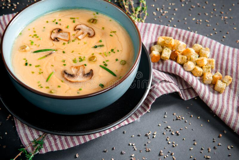Sopa deliciosa de creme de cogumelo com campeões na mesa cinza imagem de stock