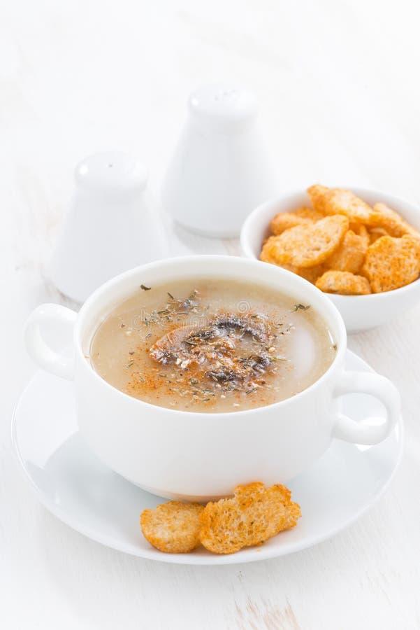 Sopa deliciosa de la crema de la seta con los cuscurrones en la tabla blanca fotos de archivo