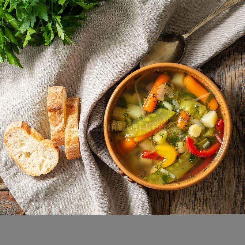Sopa dietética vegetal do vegetariano da mola brilhante Vista superior, fundo de madeira rústico marrom, guardanapo de linho fotos de stock