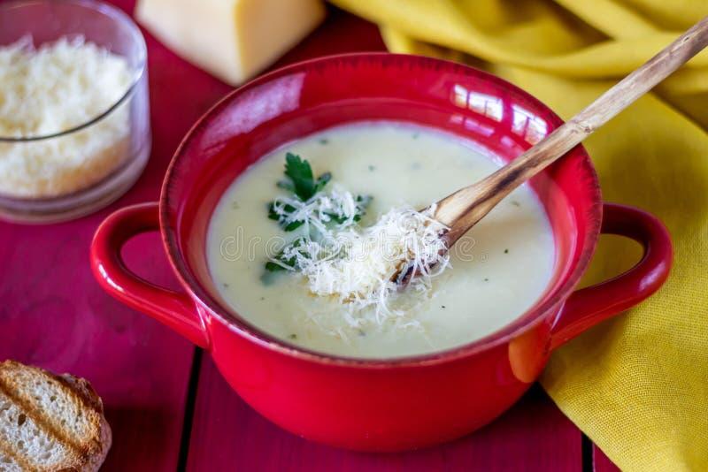 Sopa do creme do queijo em um fundo de madeira vermelho Fritos de p?o do p?o branco ingredientes foto de stock royalty free