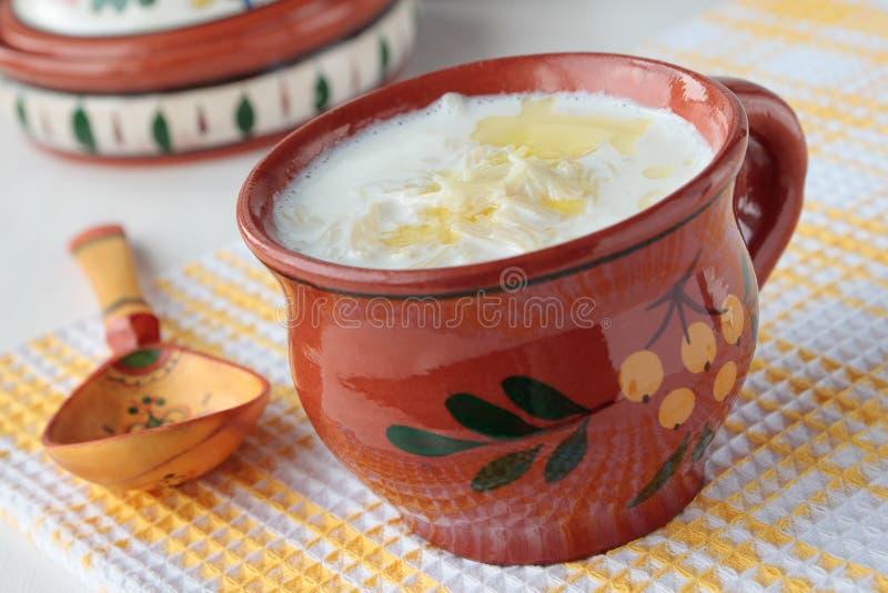 Sopa do leite com os macarronetes no copo imagens de stock royalty free