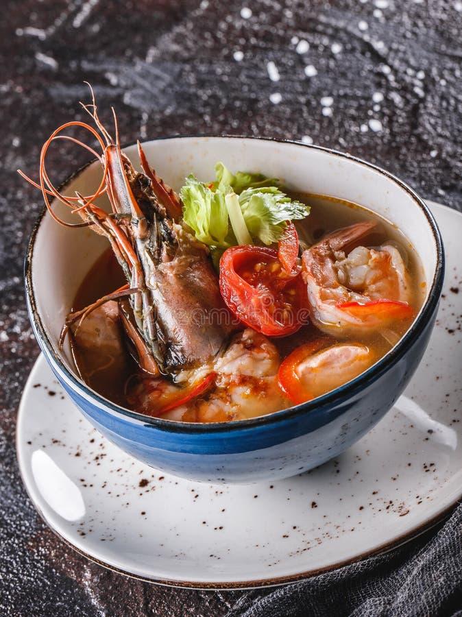 Sopa do marisco com langoustine, mexilhões, calamar, salmões da faixa, camarão e aipo na bacia sobre o fundo escuro Alimento saud imagens de stock
