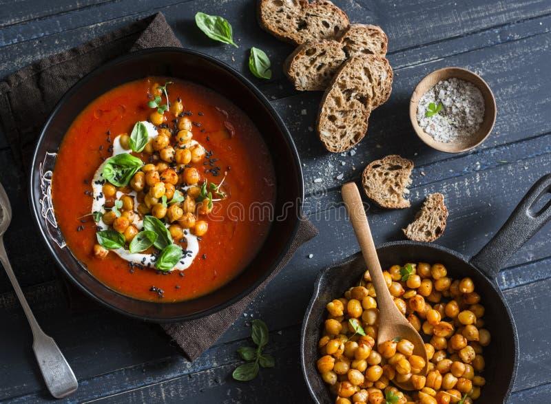 Sopa do tomate com os grãos-de-bico fritados picantes em uma tabela de madeira escura, vista superior Alimento saudável do vegeta fotos de stock