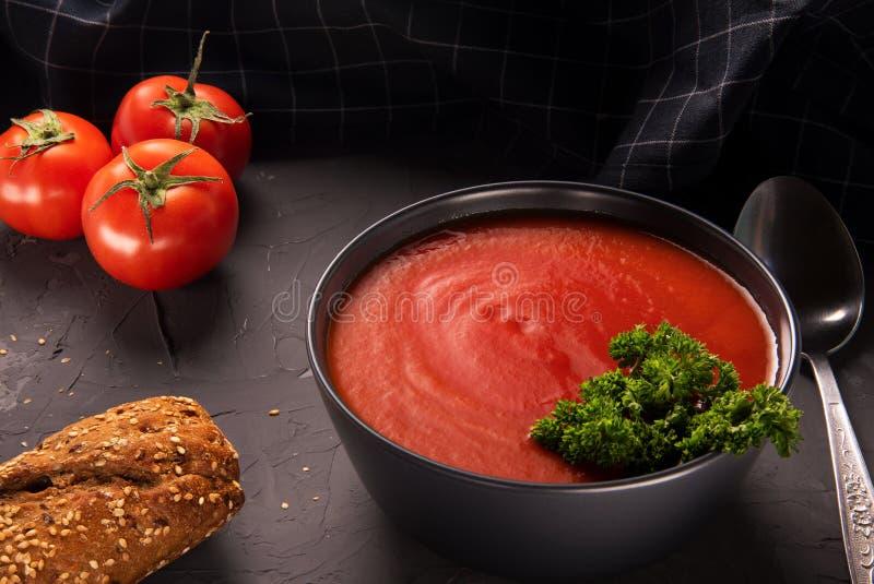 Sopa do tomate em uma bacia preta no fundo de pedra cinzento foto de stock royalty free