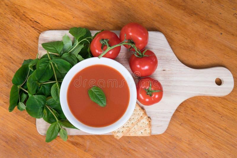 Sopa do tomate na tabela com ingredientes imagens de stock