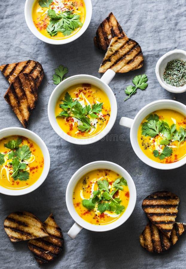 Sopa do vegetariano da abóbora da cúrcuma no fundo cinzento, vista superior A sopa lisa da polpa de butternut da configuração ser imagem de stock