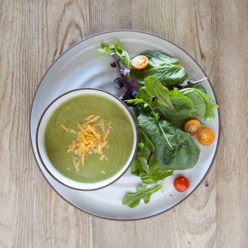 Sopa dos brócolis e do queijo e salada verde imagem de stock
