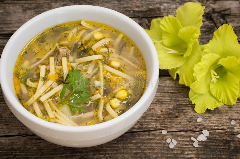 Sopa e milho de macarronete da galinha na tabela de madeira velha Vista superior Close-up fotografia de stock royalty free