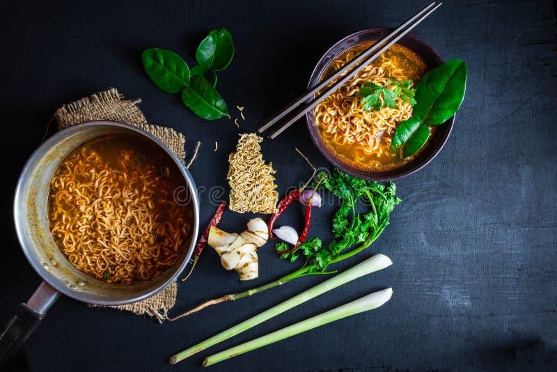 Sopa e vegetais de macarronetes imediatos picante em um fundo preto fotografia de stock