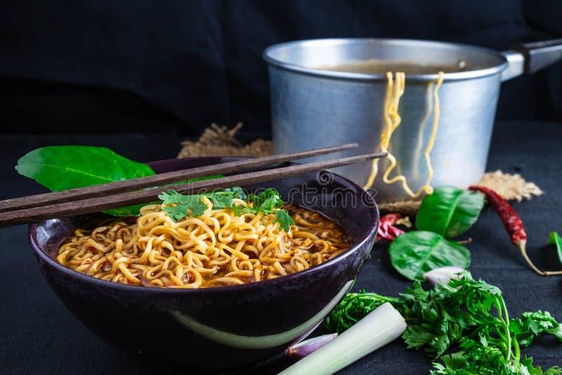 Sopa e vegetais de macarronetes imediatos picante em um fundo preto fotografia de stock royalty free
