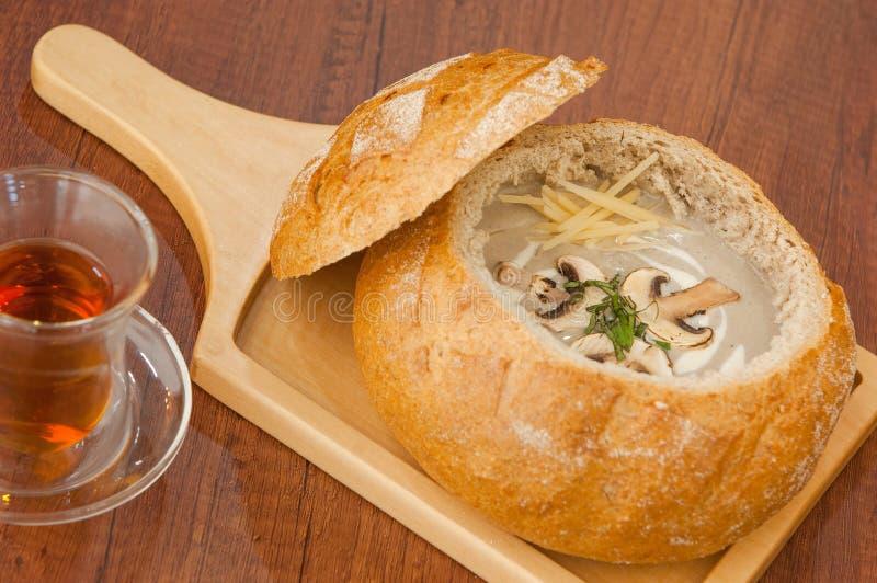 Sopa en un cuenco del pan en el tablero imágenes de archivo libres de regalías
