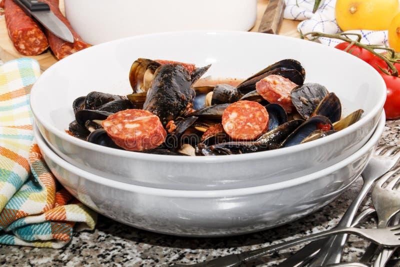 Sopa espanhola do mexilhão com molho cortado do chouriço e de tomate fotografia de stock