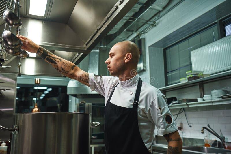 Sopa famosa Opinião lateral o cozinheiro chefe calvo atrativo no avental que toma uma concha para a sopa que cozinha ao estar em  imagem de stock royalty free